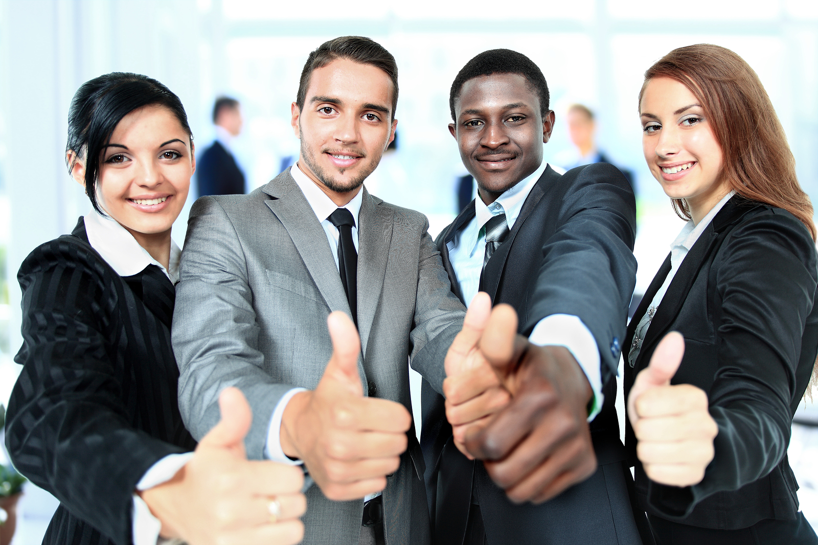 Happy business team with thumbs up in the office | Recruiteze